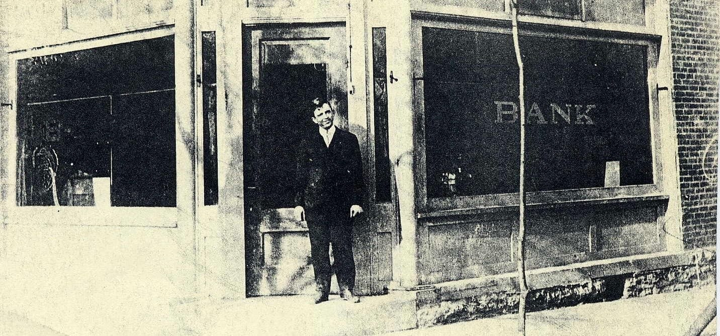 Man standing outside an old bank.
